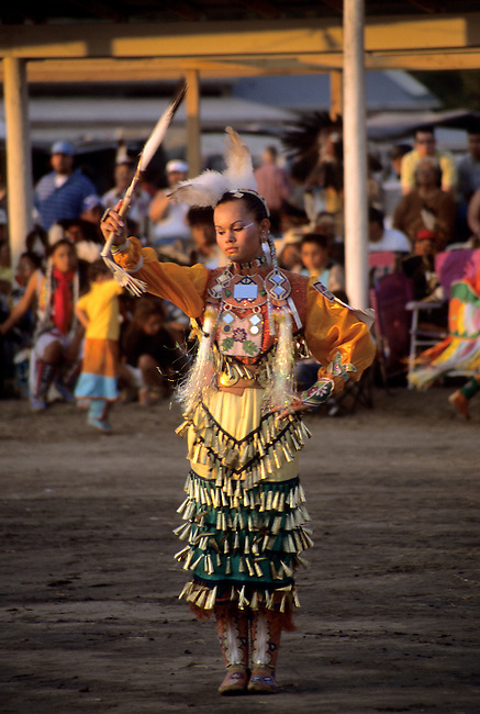 Teenage girl dressed in a jingle dress danced with an eagle feather fan during a pow wow.