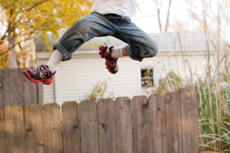 My older son, age six, leaps over a fence in our backyard while playing freeze tag with me.