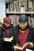 Young Bangladeshi women read books in Church Street library, Paddington, London.