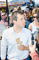 South Bend mayor and Democratic presidential candidate Pete Buttigieg eats a pork loin on a stick at the Iowa State Fair in Des Moines, Iowa, on Tues., Aug. 13, 2019.