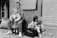 England. Greater Manchester. Salford. A young mother and her two daughters are seated on their luggages waiting for a bus to arrive. The mother is part of the Spinners group, a women's association which help families and women with children living in poverty. The family is set to go on a week holiday thanks to the Spinners association. Salford is a city in the Metropolitan Borough of Salford in Greater Manchester. North West England is one of nine official regions of England. © 1990 Didier Ruef