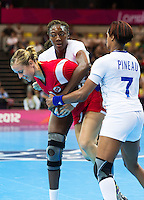 28 JUL 2012 - LONDON, GBR - Tonje Nøstvold (NOR) of Norway (left, in red) finds her path to goal blocked by Mariama Signate (FRA) (centre, in white) and Allison Pineau (FRA) of France (right, in white)  during the women's London 2012 Olympic Games Preliminary round handball match at The Copper Box in the Olympic Park, in Stratford, London, Great Britain (PHOTO (C) 2012 NIGEL FARROW)