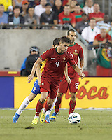 Portugal midfielder Miguel Veloso (4) centers the ball. In an international friendly, Brazil (yellow/blue) defeated Portugal (red), 3-1, at Gillette Stadium on September 10, 2013.