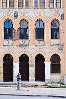 Building in Mostar damaged by the war and still not renovated. Ruined by bullet holes, mortar bomb shell grenade damage, very close to the beautifully renovated old town city centre. Mostar's most prominent Orientalist building Franc Blazek's Gymnasium built in 1902 with classical proportions and Islamic details. Town of Mostar. Federation Bosne i Hercegovine. Bosnia Herzegovina, Europe.