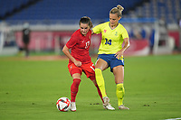 YOKOHAMA, JAPAN - AUGUST 6: Jessie Fleming #17 of Canada battles for the ball with Nathalie Bjorn #14 of Sweden during a game between Canada and Sweden at International Stadium Yokohama on August 6, 2021 in Yokohama, Japan.