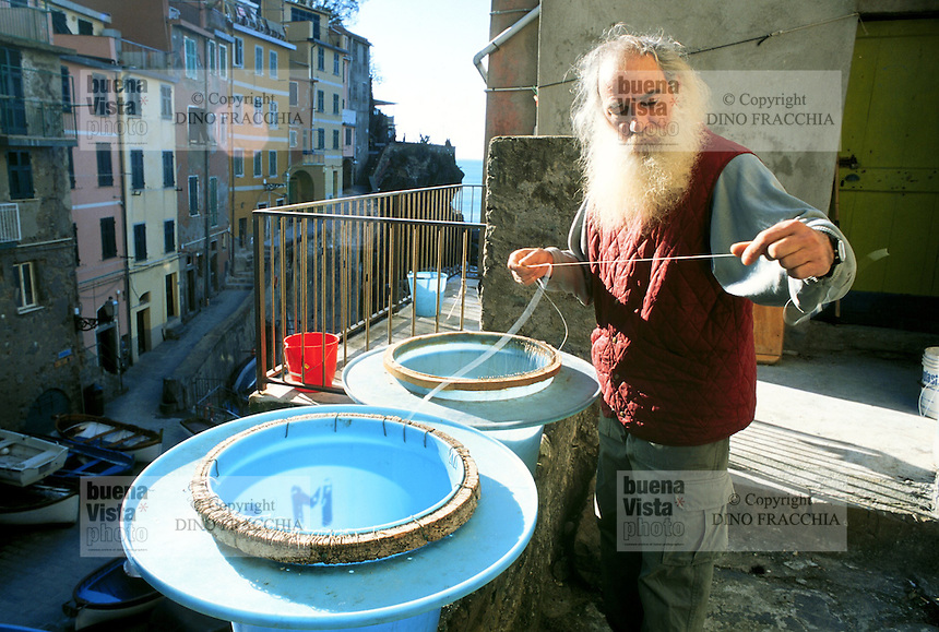 - old fisherman repairs fishing-line in Riomaggiore (Cinque Terre)....- anziano pescatore ripara le lenze a Riomaggiore (Cinque Terre)