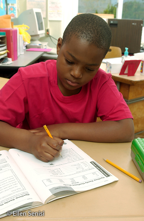 MR / Schenectady, NY / .Yates Arts in Education Magnet School / urban public elementary school / Grade 5.Boy (10, African-American) writes in reading workbook during independent work time.  Independent work is usually preparation or follow-up for reading or math class lessons done at a different time the same day. .MR: AD-g5a Dra1..© Ellen B. Senisi