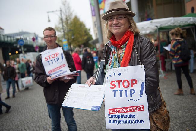 """Am Samstag den 11. Oktober 2014 protestierten europaweit Menschen gegen das geplante Freihandelsabkommen zwischen den USA und der EU, TTIP. Sie sammelten, trotz der Ablehnung der Europaeischen Kommission Unterschriften fuer die europaeische Buergerinitiative gegen TTIP (im Bild). Die europaeische Buergerinitiative will mit der Unterschriftensammlung ein Volksbegehren gegen TTIP initiieren. Das umstrittene Freihandelsabkommen beinhaltet u.a. Sondergerichte fuer Konzerne, die ausserhalb der Gerichtsbarkeit der europaeischen Laender stehen, einne Absenkung der Umwelt-, Verbraucherschutz- und Datenschutzstandards auf US-Niveau und auch die massenhafte Einfuhr von gentechnisch manipulierten Lebensmitteln.<br /> In Berlin-Prenzlauerberg wurde die Unterschriftensammlung mit einem satirischen Theaterstueck der """"Tea-Tip-Party Deutschland"""" begleitet. Motto des Stueckes """"Trinken Sie mit uns, denn wir haben einen Grund zum Feieren! - Sie nicht, aber das ist egal.""""<br /> Rechts im Bild: Gerlinde Schermer, SPD-Berlin.<br /> 11.10.2014, Berlin<br /> Copyright: Christian-Ditsch.de<br /> [Inhaltsveraendernde Manipulation des Fotos nur nach ausdruecklicher Genehmigung des Fotografen. Vereinbarungen ueber Abtretung von Persoenlichkeitsrechten/Model Release der abgebildeten Person/Personen liegen nicht vor. NO MODEL RELEASE! Don't publish without copyright Christian-Ditsch.de, Veroeffentlichung nur mit Fotografennennung, sowie gegen Honorar, MwSt. und Beleg. Konto: I N G - D i B a, IBAN DE58500105175400192269, BIC INGDDEFFXXX, Kontakt: post@christian-ditsch.de<br /> Urhebervermerk wird gemaess Paragraph 13 UHG verlangt.]"""