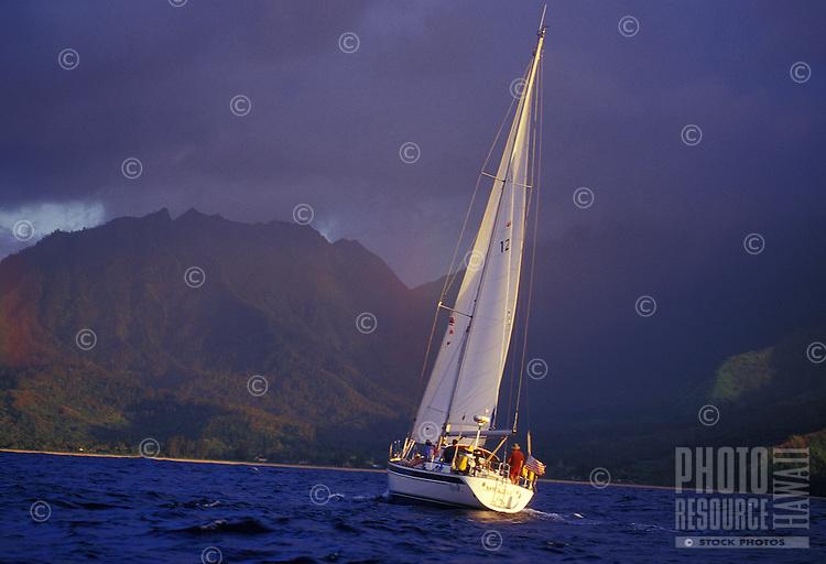 Family sailing a 48 foot cruising yacht off Hanalei bay, north Shore of Kauai, Hawaii