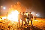 "© Joel Goodman - 07973 332324 . 23/10/2016 . Calais , France . Riot police charge residents at the Calais migrant camp known as "" The Jungle "" , in Northern France , on the evening before the start of the eviction and destruction of the camp . Photo credit : Joel Goodman"