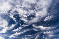 Clouds drift across a deep blue sky late on a summer afternoon.