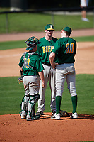 Siena Saints pitching coach Steve Adkins (center) talks with starting pitcher Dylan D'Anna (30) and catcher Alex Milone (10) during a game against the UCF Knights on February 17, 2019 at John Euliano Park in Orlando, Florida.  UCF defeated Siena 7-1.  (Mike Janes/Four Seam Images)