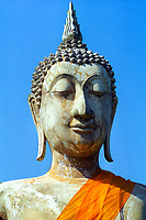 Wat Chana Songkhram temple, sculpted Buddha head with an orange robe and a blue sky background, in Sukhothai Historical Park, Thailand, Southeast Asia