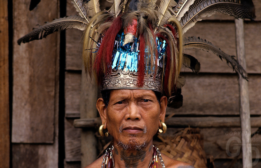 An Iban warrior in Sarawak, Borneo, Malaysia wearing his collection of various chains and ornaments including the unusual head dress