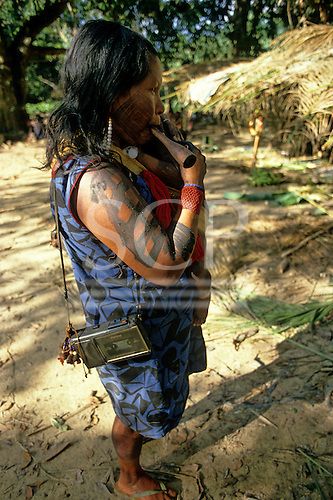 Altamira, Brazil. Kayapo Indian woman with a cassette tape recorder  over her shoulder with genipapo body paint and a chillom pipe.
