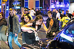 """© Joel Goodman - 07973 332324 . 17/12/2016 . Manchester , UK . A woman pulls another woman away , as the second woman strikes the bonnet of a cab with her hand . Revellers out in Manchester City Centre overnight during """" Mad Friday """" , named for being one of the busiest nights of the year for the emergency services in the UK . Photo credit : Joel Goodman"""
