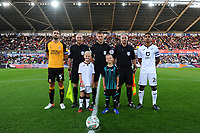 Greg Taylor of Cambridge United and Kyle Naughton of Swansea City with mascots during the Carabao Cup Second Round match between Swansea City and Cambridge United at the Liberty Stadium in Swansea, Wales, UK. Wednesday 28, August 2019.
