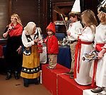 """Washington, CT- 29 December 2013-122913CM16  CL ONLY PLEASE---- Carol Elizabeth Skog, local author of  Enchantment Ädventyr, H.C.A. and I Understand helps Darya Abraham, 2, of Washington who played """"Tomte"""" with a lantern, as other children who dressed up for a miniature procession of Sankta Lucia look on, inside the Gunn Memorial Library in Washington on Sunday.   Christopher Massa Republican-American"""