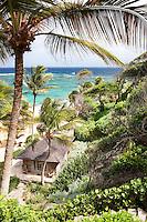 An elevated view of a beach house set amongst a tropical garden.