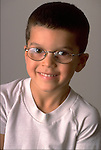 portrait of smiling young boy with glasses