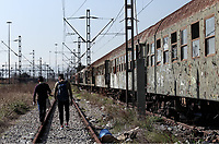Pictured: Two men walk on the tracks at the OSE freight depot in Thessaloniki, Greece. Wednesday 05 April 2017<br /> Re: A year after an agreement was signed between Greece and Turkey for the management of refugees. Migrants, mostly from Morocco, Algeria and Tunisia, have been living in disused train carriages at the Thessaloniki freight depot of OSE in northern Greece, the company managing the railways in the country. Some of the migrants climb onto moving trains, or even hide themselves in storage areas, hoping that they will cross the border.
