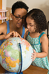 Three year old girl at home with mother, looking at globe and talking about where family came from