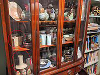 BNPS.co.uk (01202 558833)<br /> Pic: AdamPartridgeAuctioneers/BNPS<br /> <br /> Pictured: Glass cabinet in the living room features a porcelain sculpture by Ruth Duckworth (bottom left) with a central disc and square porcelain basket (middle shelf), made circa 1975 by Gillian Lowndes.<br /> <br /> A huge collection of pottery and ceramics found stacked inside the suburban home of an elderly couple has sold for almost £200,000.<br /> <br /> Leonard and Alison Shurz filled every room of their three bed house with ceramic pieces they had gathered from all over the world.<br /> <br /> The Aladdin's Cave of pots, bowls, plates, vases and jugs was found by a stunned auctioneer who had the daunting task of cataloguing it all.