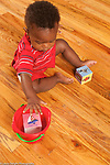 13 month old baby boy sitting on floor playing with bucket and blocks