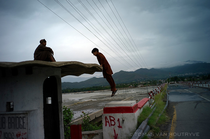 A boy climbs up on a guard post at the start of a bridge over the Swat river that was destroyed by floods in Mingora, Swat valley, Pakistan, on Aug. 26, 2010.  According to Pakistani officials, every major bridge over the Swat river was destroyed by the floods.