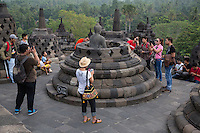 Borobudur, Java, Indonesia.  Early-morning Tourists Gathered around a Statue of Buddha in an uncovered Stupa.