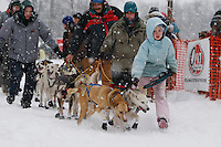 A young handler helps Travis Beals of Seward to the start line of the 2009 Junior Iditarod on Knik Lake on Saturday Februrary 28, 2009.