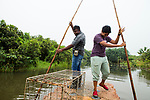 Fishing Cat (Prionailurus viverrinus) biologists, Maduranga Ranaweera and Anya Ratnayaka, carrying box trap for collaring on boat in urban wetland, Urban Fishing Cat Project, Diyasaru Park, Colombo, Sri Lanka