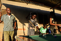 TANZANIA Geita, artisanal gold mining in Mgusu, where about 4000 people live and work, young miner play billiards after work  / TANSANIA Geita, kleine Goldminen in Mgusu, hier arbeiten und leben ca. 4000 Menschen, junger Bergleute spielen Billard nach der Arbeit