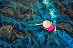 Worker mends fish nets Chanwit Wanset