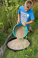 Sandbad für Spatzen im Garten, Spatz, Sperling, eine Schale wird mit Sand gefüllt und gibt Spatzen die Möglichkeit, im Sand zu baden, Spatzen-Sandbad, Sandy bath for sparrows in the garden, sparrow, a bowl is filled with sand and gives to sparrows the possibility to have a bath in the sand, sparrow-sandy bath
