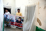 13 April 2013, Karachi, Pakistan:  Students Hassan Turapi , (25 left)  and Ashraf Saqib, 22, with a poster of their friends who were killed in the Shia dominated Abbas Town, Karachi,  where 40 days earlier a massive car bomb flattened the surrounding apartment blocks killing and injuring scores of both Sunni and Shia residents. Karachi is a city wracked by violence and many fault lines that span Taliban infiltration, mafia rackets, sectarian violence and corruption from politicians and security forces. Picture by Graham Crouch/The Australian