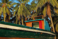 Colorful fishing boat surrounded by palm tress, Maldives.