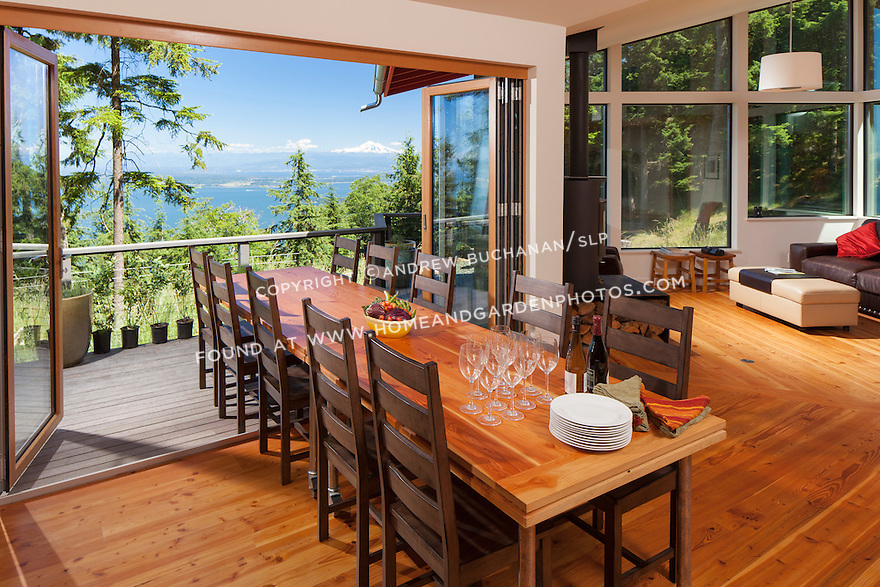 Outdoor living with folding French doors open wide and the large dining table half way out onto the porch.