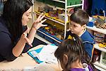 Afterschool homework help program for Headstart graduates Grades K-3 female teacher working with kindergarten students