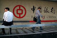 Pedestrians walk past a Bank of China branch in Shenzhen, China. .