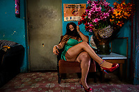 "A Mexican sex worker, working under the nickname ""La Mexicana"", poses for a picture while waiting for clients in a street sex bar in San Salvador, El Salvador, 16 November 2016. Although prostitution is not legal in El Salvador, dozens of street sex workers, wearing provocative miniskirts, hang out in the dirty streets close to the capital's historic center. Sex workers of all ages are seen on the streets but a significant part of them are single mothers abandoned by their male partners. Due to the absence of state social programs, they often seek solutions to their economic problems in sex work. The environment of street sex business is strongly competitive and dangerous, closely tied to the criminal networks (street gangs) that demand extortion payments. Therefore, sex workers employ any tool at their disposal to struggle hard, either with their fellow workers, with violent clients or with gang members who operate in the harsh world of street prostitution."