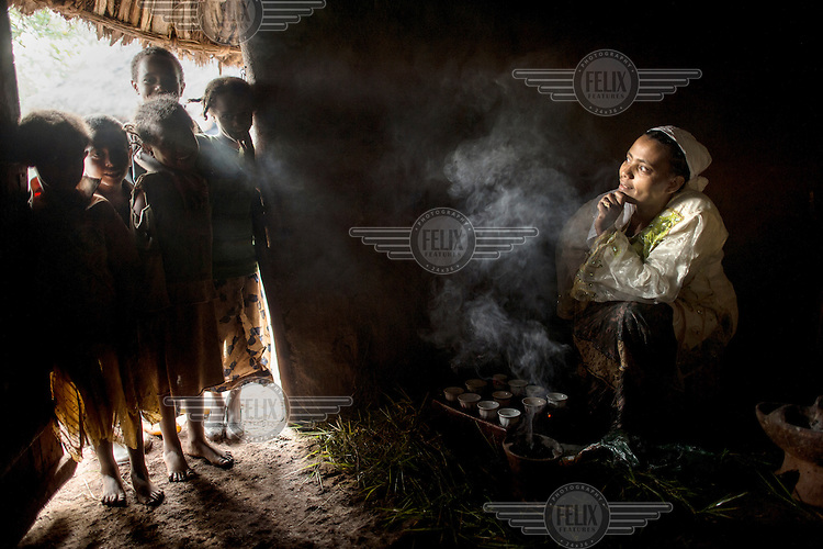 A group of young children look on as  Ramla Sharif roasts coffee in a charcoal brazier inside her home in the village of Choche. /Felix Features