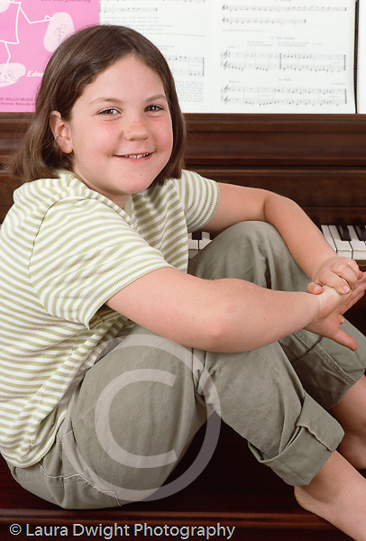 girl,8 years old portrait, sitting on piano bench Caucasian vertical