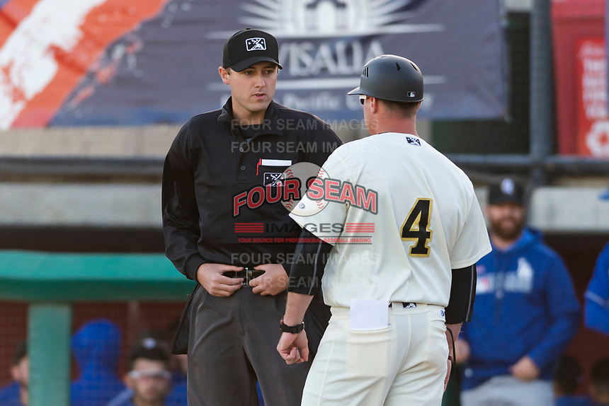 Visalia Rawhide manager Shawn Roof (4) argues a call with home plate umpire Trevor Dannegger during a California League game against the Rancho Cucamonga Quakes on April 9, 2019 in Visalia, California. Visalia defeated Rancho Cucamonga 8-5. (Zachary Lucy/Four Seam Images)
