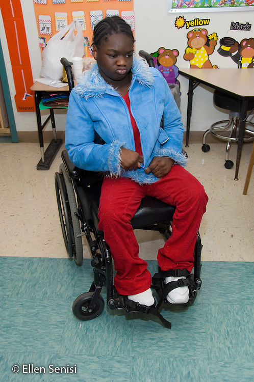 MR / Albany, NY.Langan School at Center for Disability Services .Ungraded private school which serves individuals with multiple disabilities.Child sitting in a wheelchair tries to unzip her coat herself, which is a challenge because of her neurological impairment. Girl: 10, African-American, cerebral palsy, expressive and receptive language delays.MR: And6.© Ellen B. Senisi