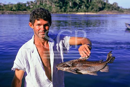 Tataquara, Amazon, Brazil. Raimundo, an Amazon man, holding a fresh caught river fish. Para State.