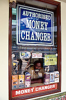 Singapore. Downtown. Town center. Orchard Road is mostly a place to shop with rows of modern shopping centres and the location for most international hotels. An indian man works in an authorised money changer place. © 2001 Didier Ruef