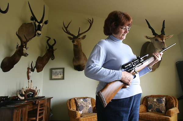 G.annieoakley.2.0213.jl.jpg/photo jamie Scott Lytle/Susan Bowers of Vista stands in her living room holding one of her guns surrounded by animals that she has shot mainly in Africa.