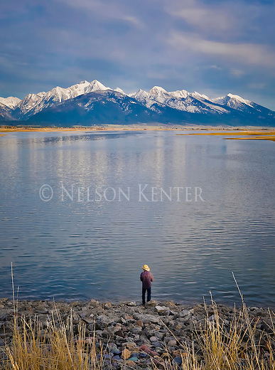 A fisherman in a straw cowboy hat and flannel shirt on the shore of Ninepipe Reservoir at the foot ofm the Mission Mountains in western Montana