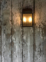 Antique light fixture on a weathered exterior facade.